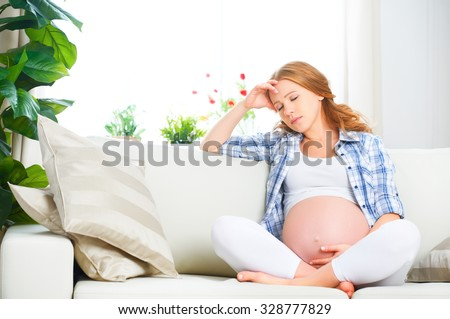 pregnant woman with a headache and pain - stock photo