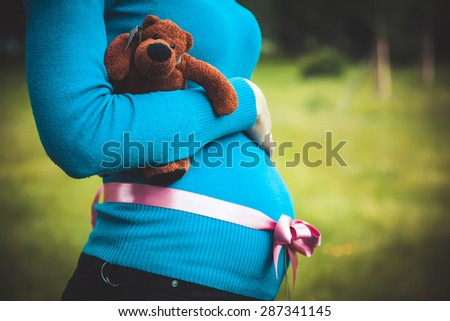 pregnant woman with a pink ribbon on her belly holding a teddy bear - stock photo