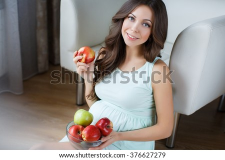 Pregnant woman with apples. Smiling pregnant woman lin bedroom.and holding apple. Beautiful young pregnant woman with apples. healthcare and beauty