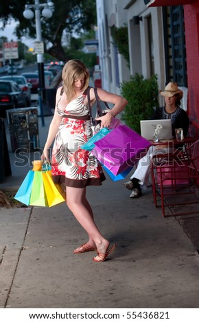 Pregnant woman with bags struggling to reach her purse - stock photo