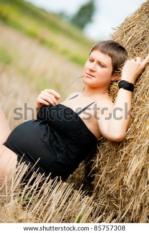 pregnant woman with big belly and straw on the field