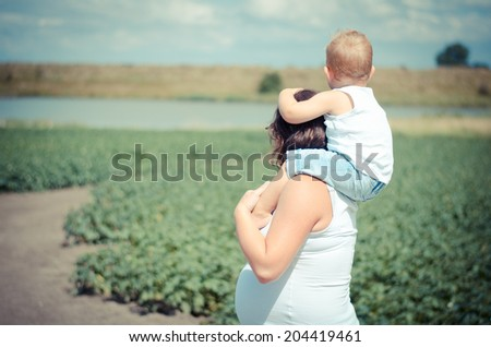 pregnant woman with boy on her neck - stock photo