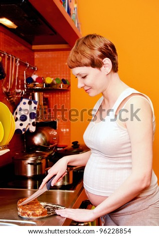 Pregnant woman with cake in kitchen - stock photo