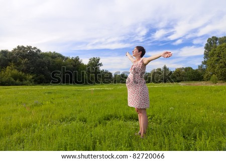 Pregnant woman with closed eyes on green meadow - stock photo