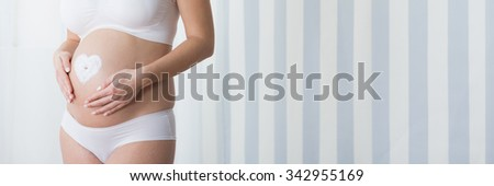 Pregnant woman with cream heart shape on belly - stock photo