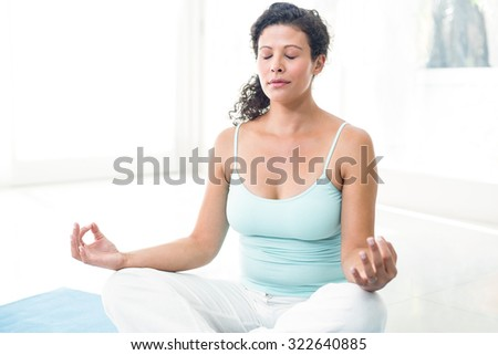 Pregnant woman with eyes closed meditating in lotus position at home - stock photo