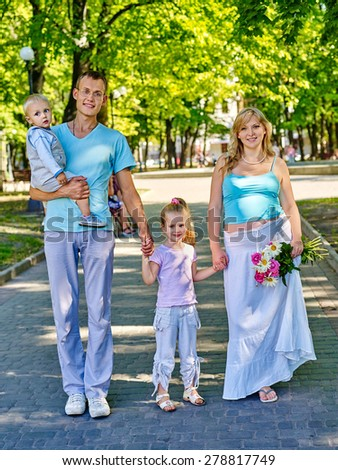 Pregnant woman  with family and two children walking outdoor in park.