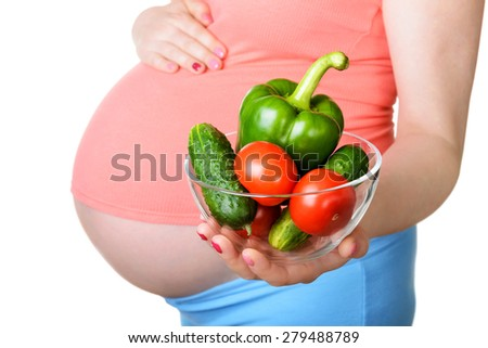 Pregnant woman with fresh vegetables isolated on white background