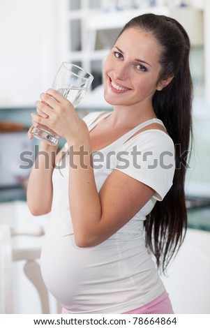 Pregnant woman with glass of water in the house kitchen.