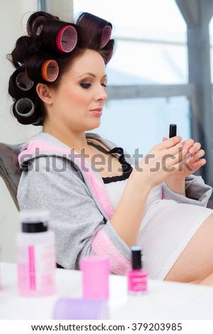 Pregnant woman with hair rollers getting nail treatment - stock photo