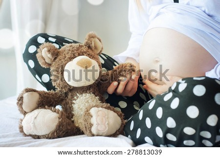 pregnant woman with hands and have bear doll - stock photo