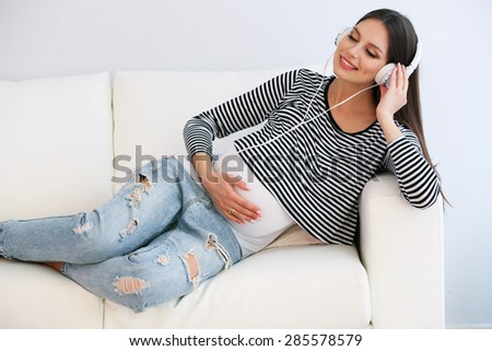 Pregnant woman with headphones on sofa in room