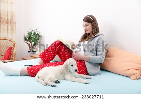 Pregnant woman with her dog at home - stock photo