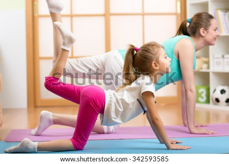 Pregnant woman with her first child doing fitness in living room - stock photo