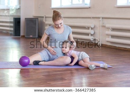 Pregnant woman with her first kid daughter doing gymnastics in living room.