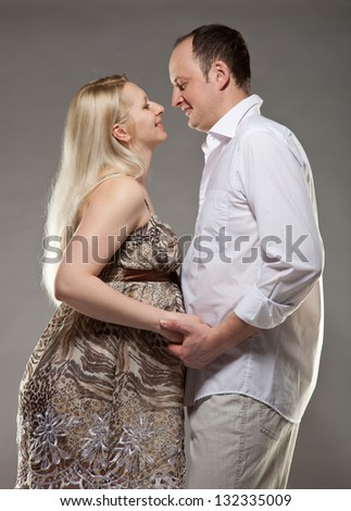 Pregnant woman with her husband, grey background - stock photo