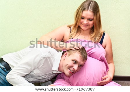 Pregnant woman with her husband hearing belly. Caucasians, a loving young couple - stock photo