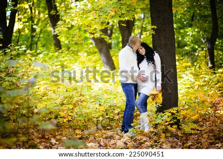 pregnant woman with her husband in the autumn forest - stock photo