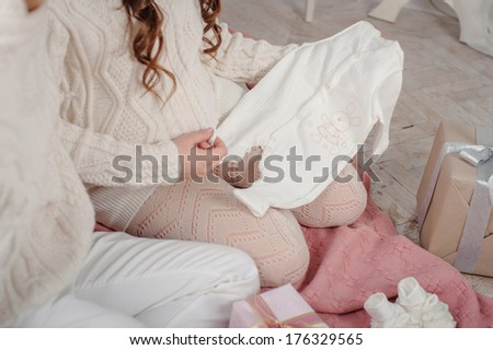 pregnant woman with her husband looking at baby shower presents - stock photo
