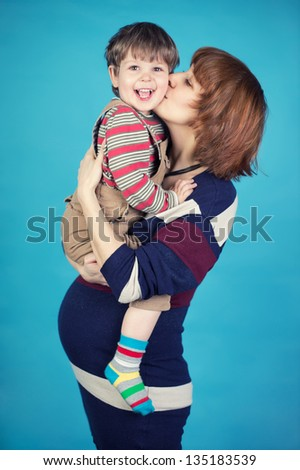 Pregnant woman with her son on blue background - stock photo