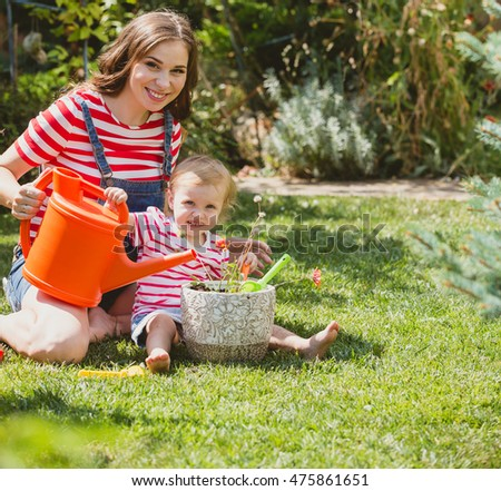 Pregnant woman with little daughter in the summer orchard cearing flower.