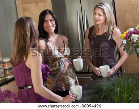 Pregnant woman with mug in kitchen with friends - stock photo