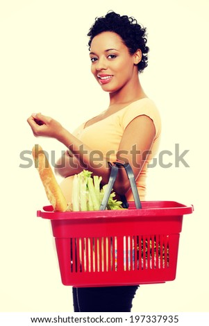 Pregnant woman with shopping basket. - stock photo