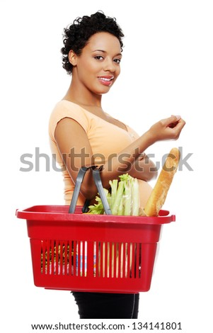 Pregnant woman with shopping basket, isolated on white - stock photo