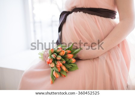 pregnant woman with tulip touching her belly  - stock photo