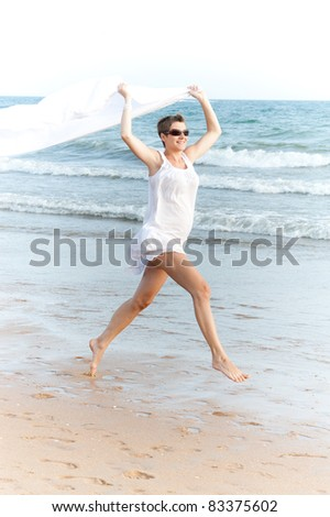 Pregnant woman with white shawl is running on the beach