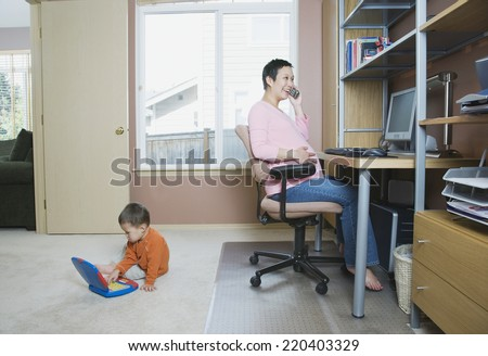 Pregnant woman working at home with young son - stock photo