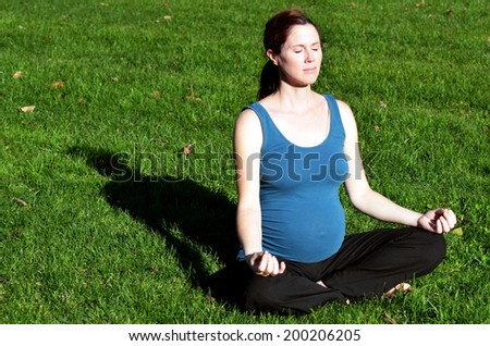 Pregnant woman yoga exercise during pregnancy outdoor at the park. Concept photo of women healthy life style and health care. copy space - stock photo