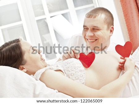 Pregnant women and her husband hands on the belly with heart symbol inside on blue window background - stock photo