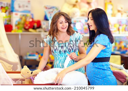 pregnant women choosing goods for baby - stock photo