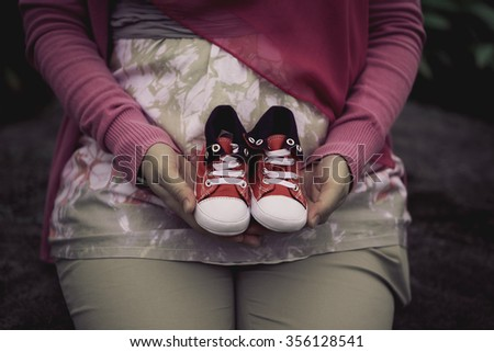 Pregnant women holding a pair of baby shoes. selective focus. - stock photo