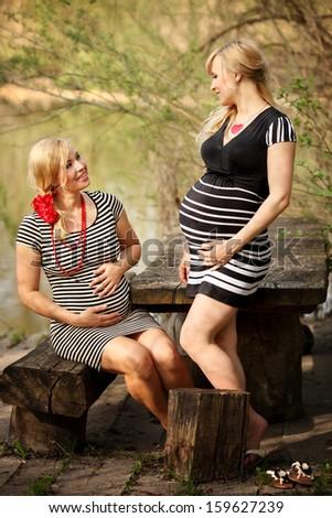 Pregnant women outdoors - stock photo