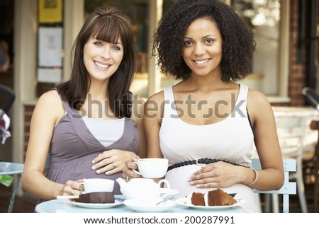 Pregnant women sitting outside cafe - stock photo