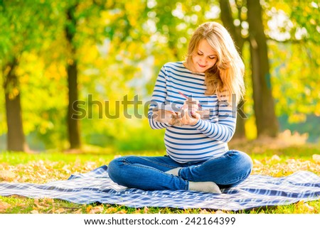 pregnant young girl makes a shopping list for the baby - stock photo