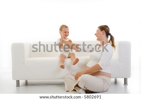 Pregnant young woman playing with a toddler sitting on a white couch...isolated view with mostly white tones. - stock photo