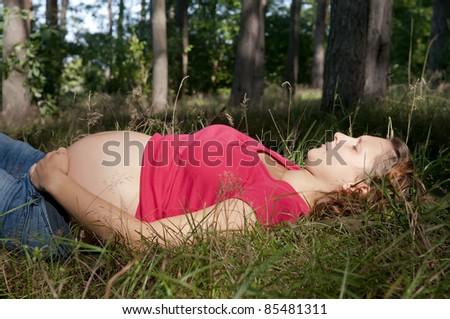 pregnant young woman relaxing in the forest - stock photo