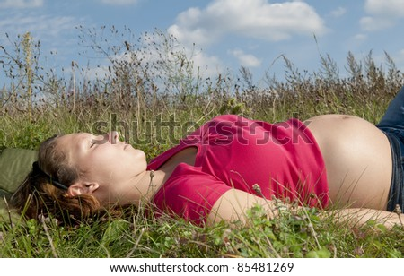 pregnant young woman relaxing on a meadow - stock photo