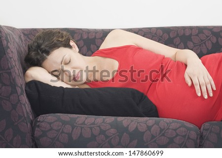 Pregnant young woman sleeping on sofa at home - stock photo