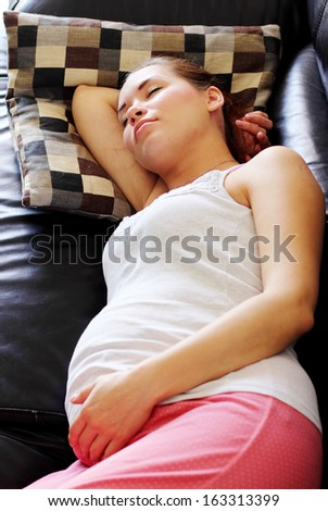 pregnant young woman sleeping on the sofa at home