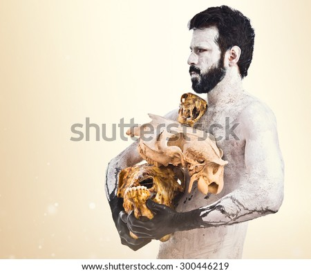 prehistoric man holding animal skulls over ocher background - stock photo