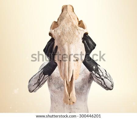 prehistoric man with horse skull over ocher background - stock photo