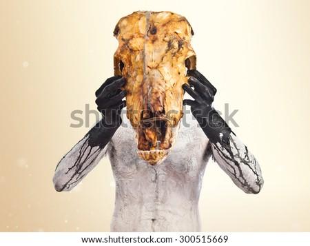 prehistoric man with veal skull over ocher background - stock photo