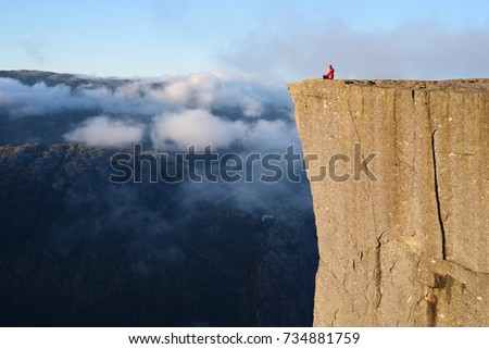 Preikestolen - amazing rock in Norway. Girl sitting on a cliff above the clouds. Pulpit Rock, the most famous tourist attraction in Ryfylke, towers over the Lysefjord