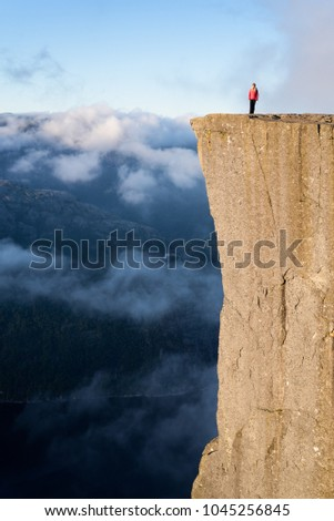 Preikestolen - amazing rock in Norway. Girl standing on a cliff above the clouds. Pulpit Rock, the most famous tourist attraction in Ryfylke, towers over the Lysefjord