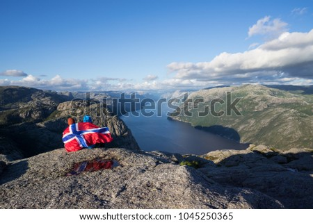 Preikestolen pathway. Couple with the flag of Norway looks at the panorama of the Lysefjord. Tourist attraction. Sunny weather in the mountains