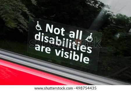 Prejudice, Not all disabilities are visible sign. A sticker with white text and wheelchair symbols stuck to the inside of a car window.
